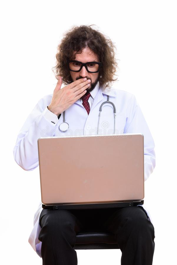 Studio shot of handsome man doctor using laptop looking shocked royalty free stock photography