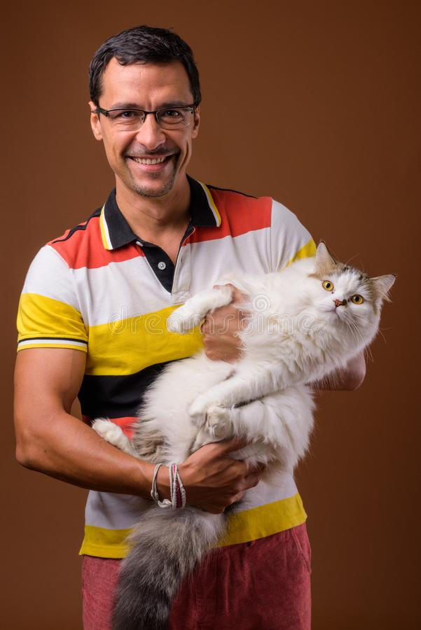 Portrait of handsome man holding Persian cat against brown background royalty free stock images