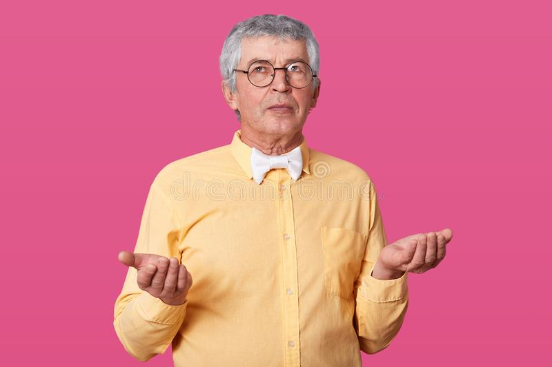 Studio shot of handsome old man wearing yellow shirt, white bow tie, and glasses, has serious facial expression, fells royalty free stock photos