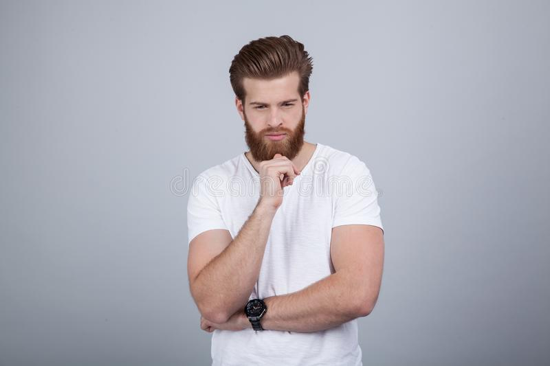 Studio shot of handsome pensive male holds chin, thinks about something, dressed in white t-shirt, stands against white background stock photography