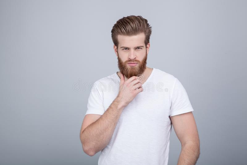Studio shot of handsome pensive male holds chin, thinks about something, dressed in white t-shirt, stands against white royalty free stock image