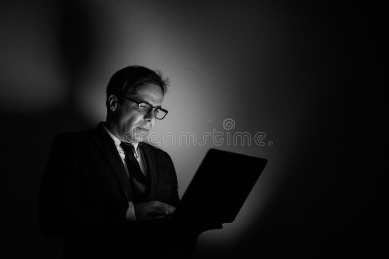Handsome Persian businessman using laptop in black and white royalty free stock image