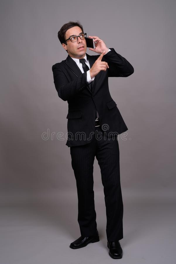 Full body shot of handsome Persian businessman using phone royalty free stock image
