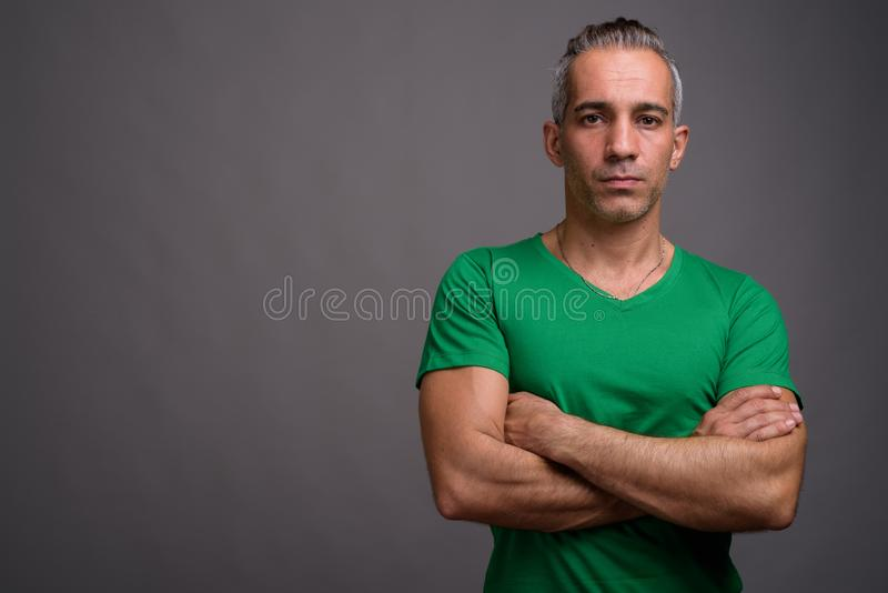Handsome Persian man with gray hair wearing green t-shirt stock photo