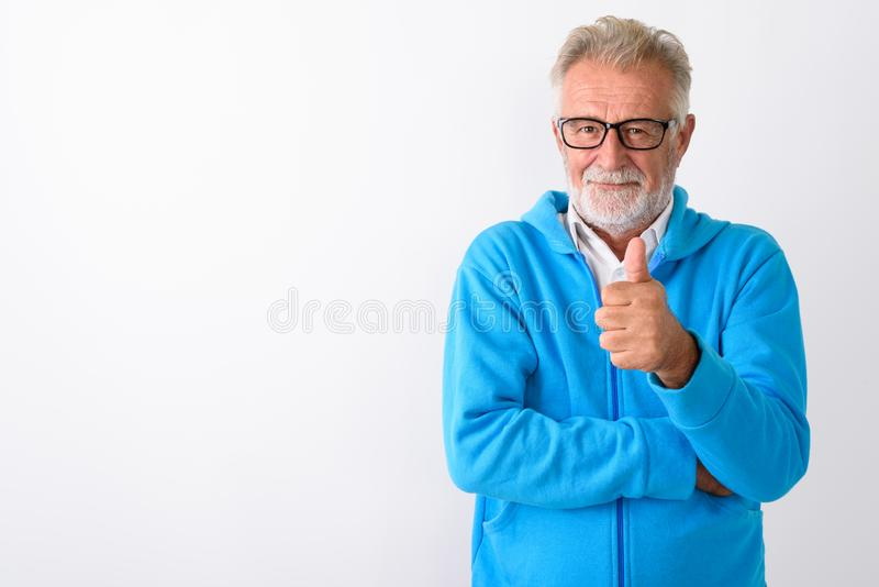 Studio shot of handsome senior bearded man giving thumb up ready. For gym against white background stock images
