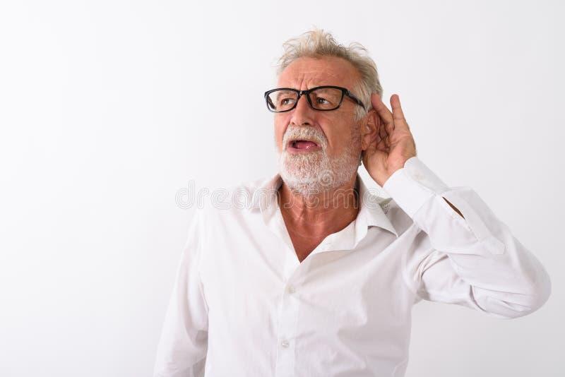 Studio shot of handsome senior bearded man listening while think. Ing and wearing eyeglasses against white background stock photography