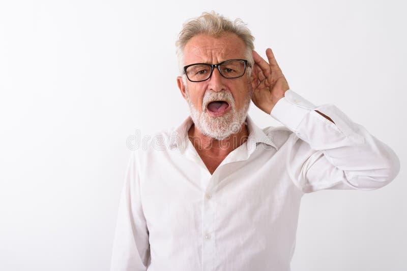 Studio shot of handsome senior bearded man listening while weari. Ng eyeglasses against white background royalty free stock image