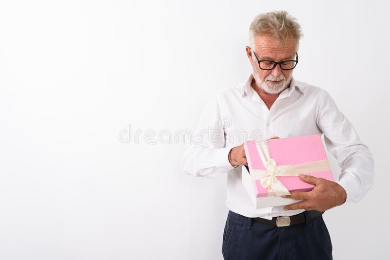 Studio shot of handsome senior bearded man opening gift box with. Eyeglasses against white background stock images