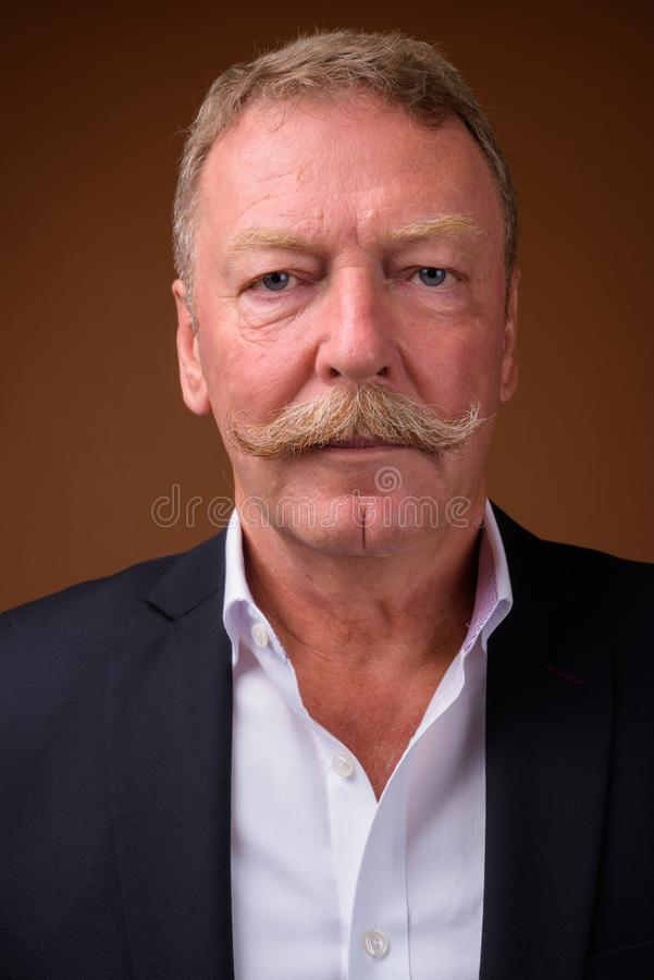 Face of senior businessman with mustache wearing suit. Studio shot of handsome senior businessman with mustache against brown background stock photos