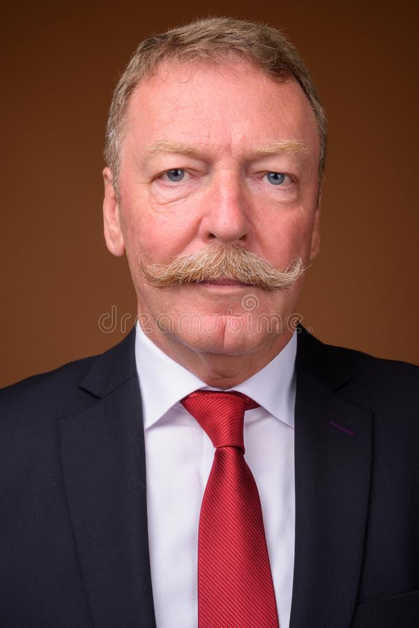 Face of senior businessman wearing suit and tie. Studio shot of handsome senior businessman with mustache against brown background stock photo