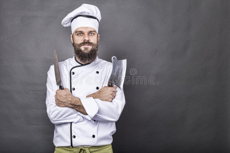 Studio shot of a happy bearded young chef holding sharp knives stock image