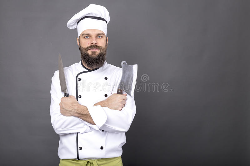 Studio shot of a happy bearded young chef holding sharp knives royalty free stock photo
