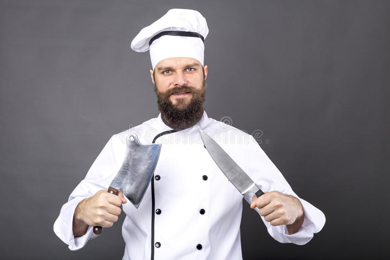 Studio shot of a happy bearded young chef holding sharp knives royalty free stock photography
