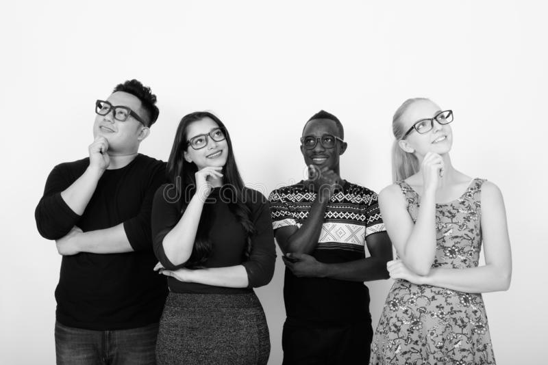 Studio shot of happy diverse group of multi ethnic friends smiling while thinking with eyeglasses together. Studio shot of multi ethnic group of friends together stock photo