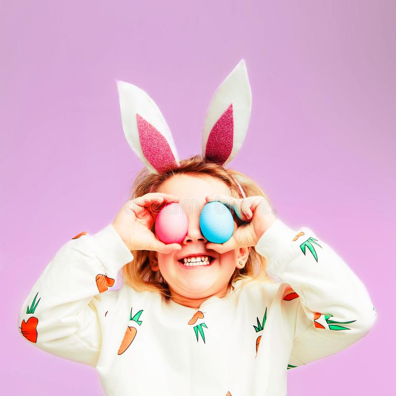 Studio shot of a happy little girl wearing bunny ears and holding up a colorful Easter egg in front of her eye. royalty free stock photo