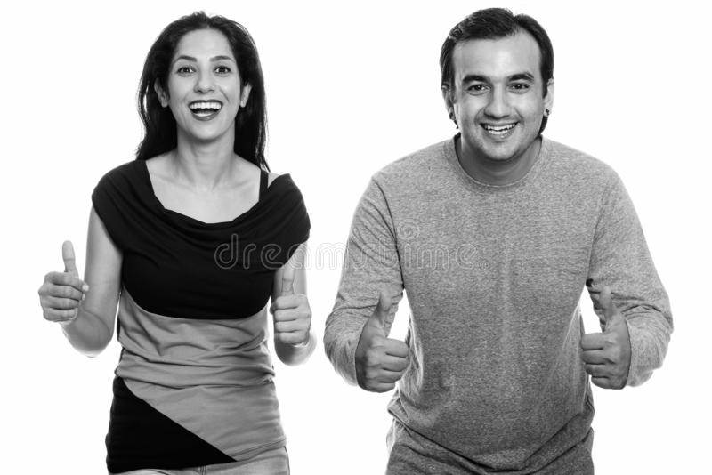 Studio shot of happy Persian couple smiling and giving thumbs up together in black and white royalty free stock images