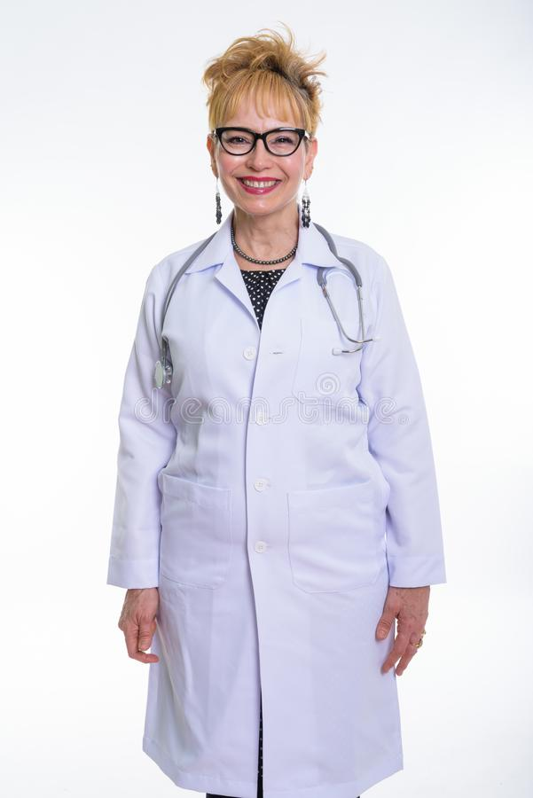Studio shot of happy senior Asian woman doctor smiling and stand royalty free stock image
