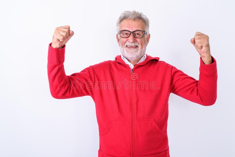 Studio shot of happy senior bearded man smiling while flexing bo. Th arms ready for gym against white background stock images