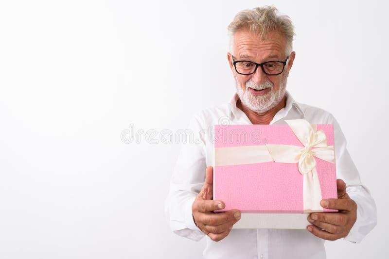 Studio shot of happy senior bearded man smiling while looking sh. Ocked while opening gift box with eyeglasses against white background stock photo