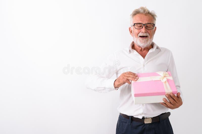 Studio shot of happy senior bearded man smiling while opening gi. Ft box eyes closed against white background royalty free stock photos