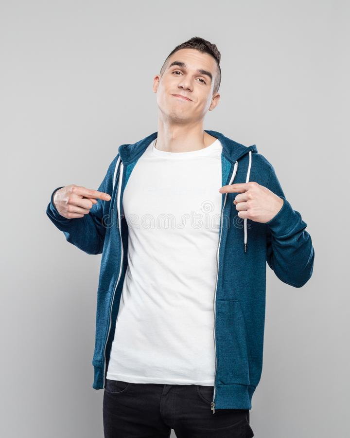 Portrait of happy young man pointing at his white t-shirt stock photo