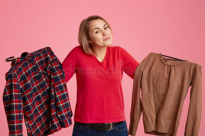 Studio shot of hesitant indecisive young Cucasian woman holds two items of clothes, cant decide what to wear this day, likes. Shopping and making purchases royalty free stock photo