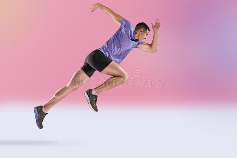 The studio shot of high jump athlete is in action. On pink background stock images