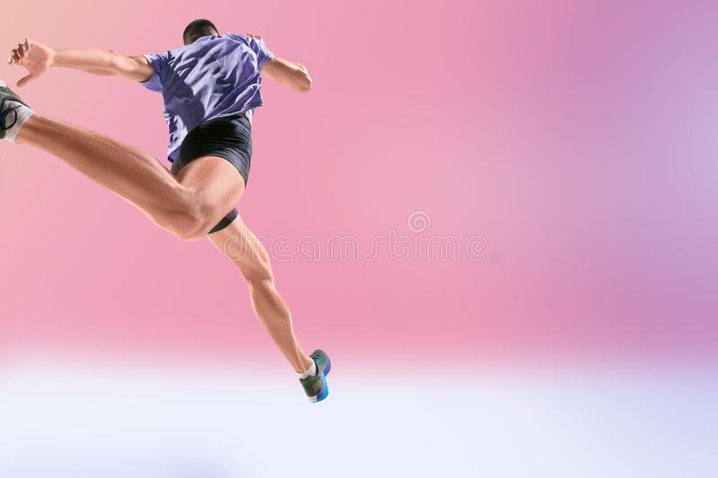The studio shot of high jump athlete is in action. On pink background stock photo