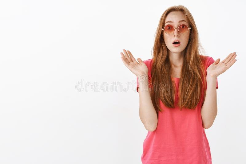 Studio shot of impressed and amazed stylish good-looking redhead girl with freckles raising spread palms and gasping royalty free stock photo