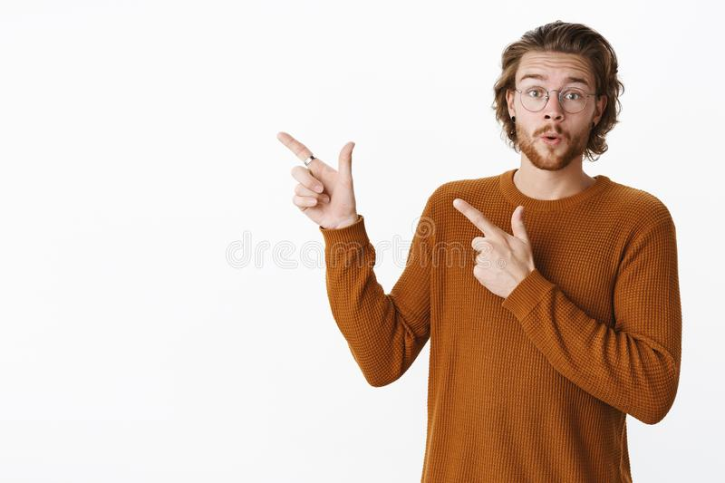 Studio shot of impressed and astonished handsome male in glasses and sweater raising eyebrows amazed folding lips in wow stock image