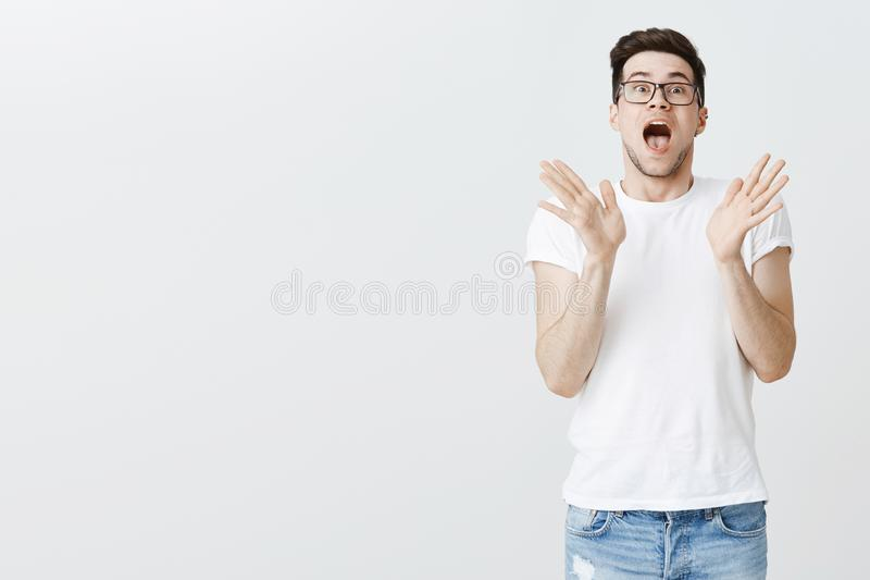 Studio shot of impressed and surprirsed charismatic young white man in glasses standing right side of copy space. Dropping jaw raising hands in amazement and stock photo