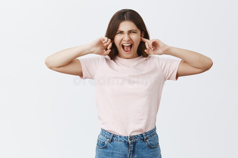 Studio shot of intense displeased attractive caucasian feminine woman in stylish outfit closing ears with index fingers royalty free stock image