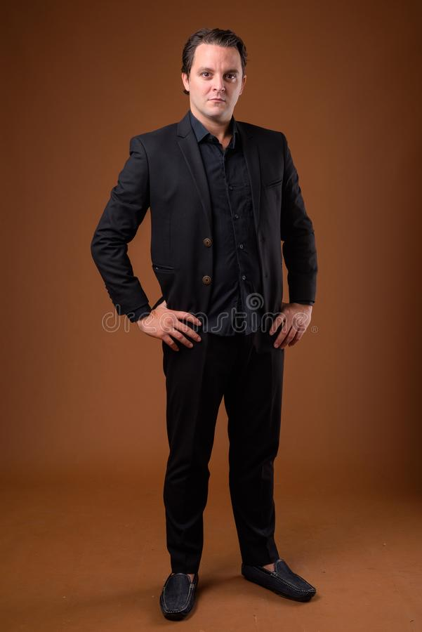 Studio shot of Italian businessman against brown background royalty free stock image