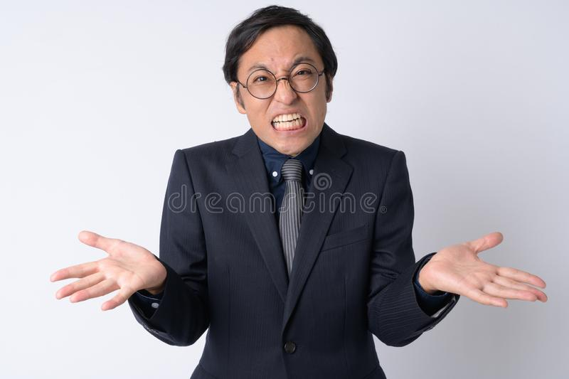 Portrait of confused Japanese businessman in suit shrugging shoulders. Studio shot of Japanese businessman wearing suit against white background stock photography
