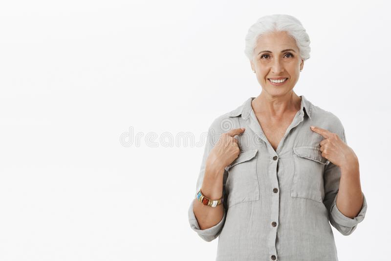 Studio shot of kind and cute elderly mother with gray hair pointing at herself with pleased and self-assured smile stock photo