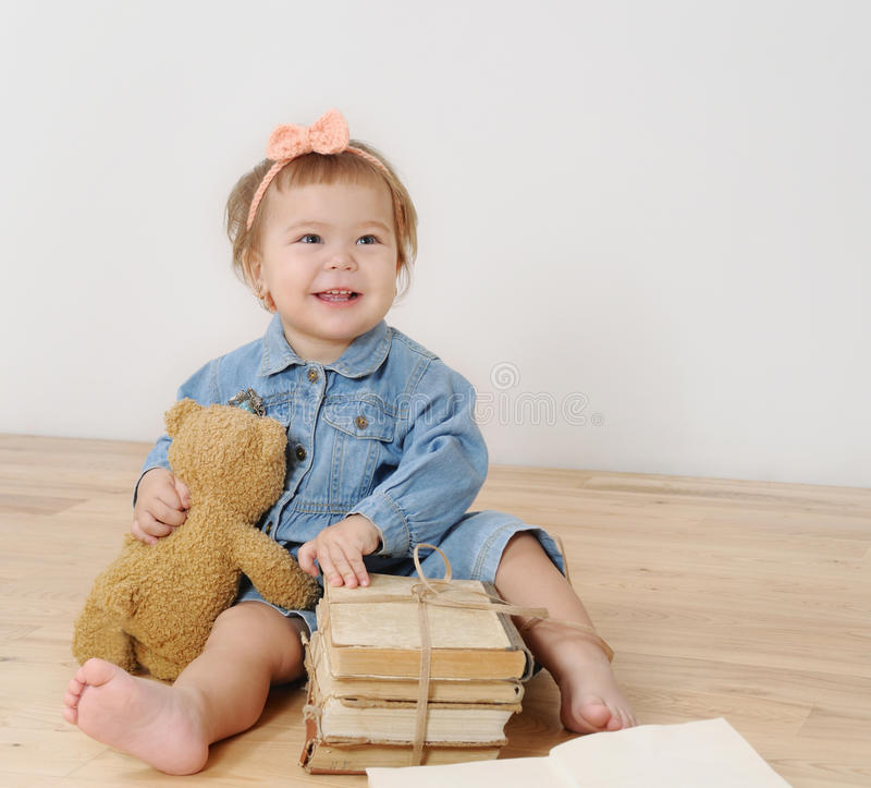 Studio shot of little cute smiling girl with his toy and books stock images