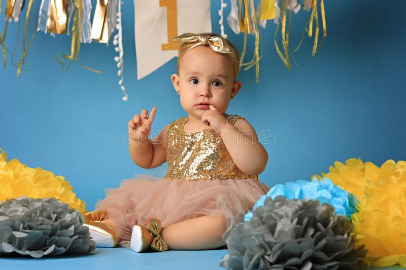 Studio shot, little girl on blue background in beautiful festive dress stock photography
