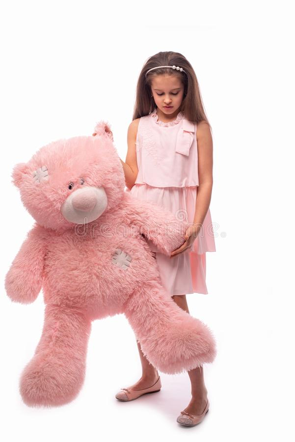 Studio shot of a little sading girl wearing in pink sundress on a white background. She is standing witn big pink toy bear,. Studio shot of a little sad girl stock images