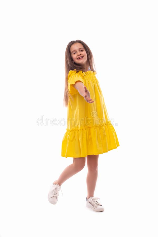 Studio shot of a little smiling girl wearing yellow sundress  on a white background royalty free stock image