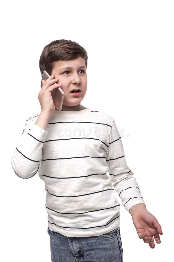 Studio shot of a little smiling  boy  talking on the phone on a white background royalty free stock image