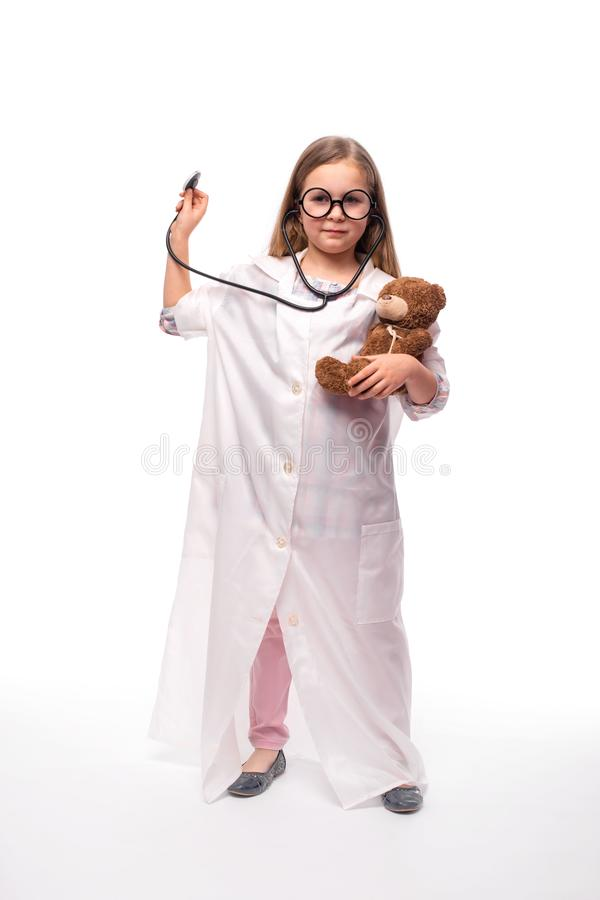 Studio shot of a little smiling girl in round glasses and white medical gown with a stethoscope treating a teddy bear ,. Studio shot of a little smiling girl in stock image