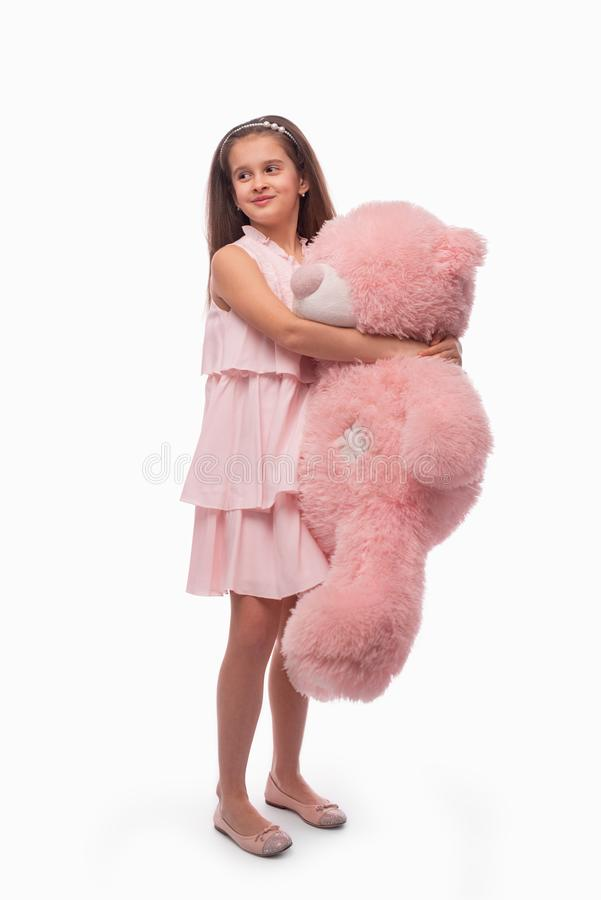 Studio shot of a little smiling girl wearibg rose sundress on a white background. She stands with a big pink toy bear in her. Hands stock images