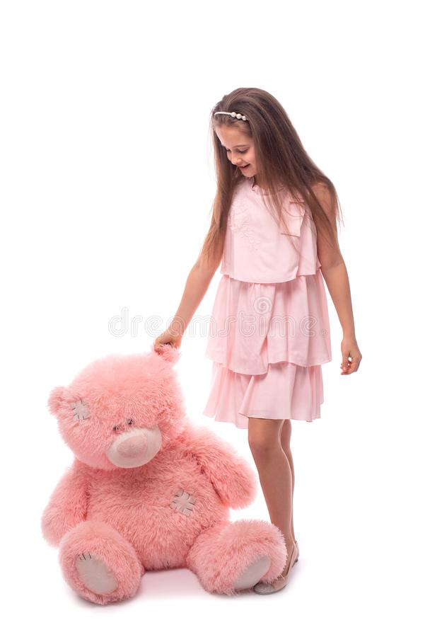 Studio shot of a little smiling girl wearing in pink sundress on a white background. She is standing witn big pink toy bear,. Studio shot of a little smiling stock images
