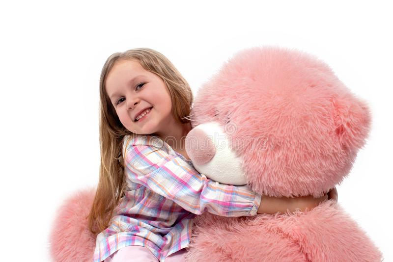 Studio shot of a smiling girl on a white background. She holds in hand big pink toy bear, isolated. Studio shot of a little smiling girl on a white background stock photo