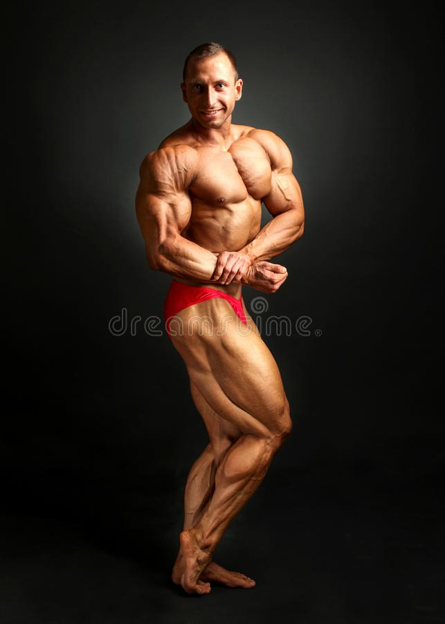 Studio shot of male bodybuilder posing, flexing and showing bice stock images