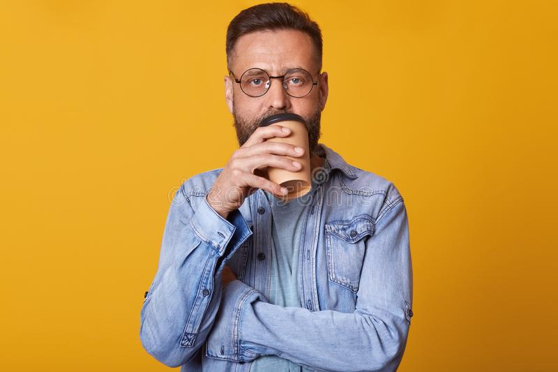Studio shot of male drinking morning coffee, standing indoor isoalted over yellow background, wearing denim jacket and glasses, royalty free stock image