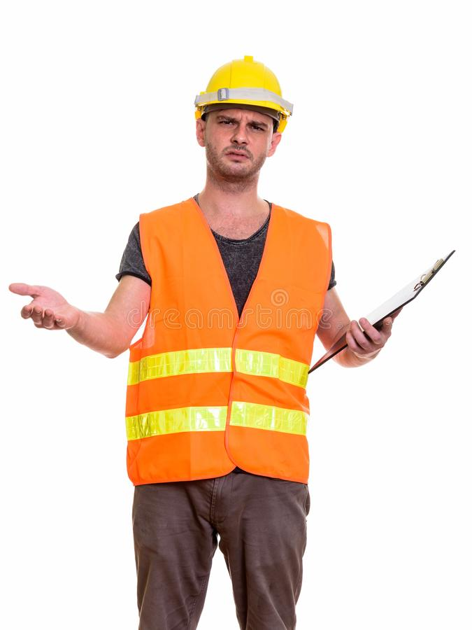 Angry young man construction worker looking confused while holdi royalty free stock photo