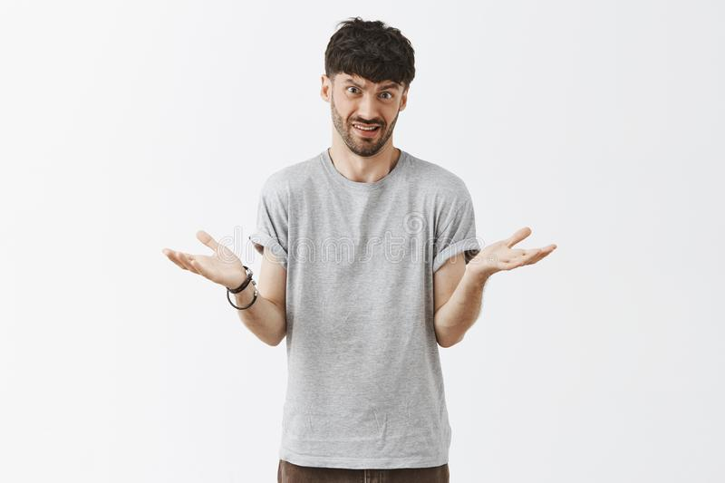 Studio shot of man explaining something simple being questioned someone cannot understand shrugging with spread palms. Frowning and grimacing with clueless stock photo