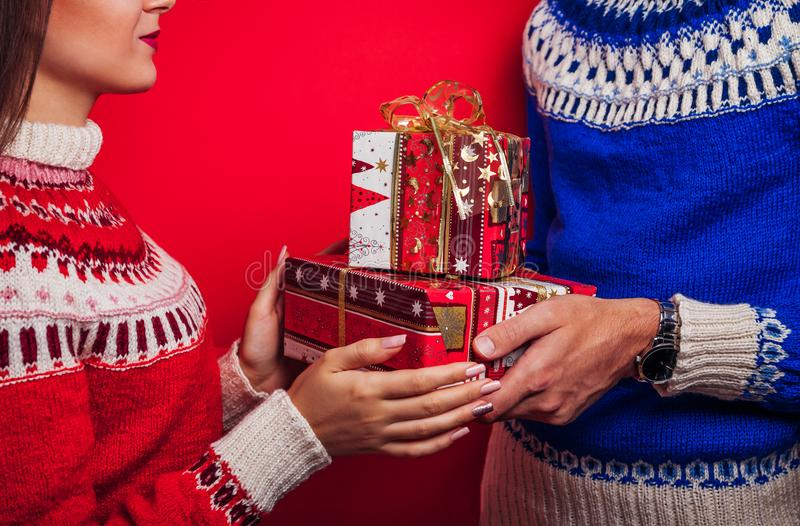 Studio shot of a man in Icelandic sweater giving his girlfriend gift boxes. Christmas or New Year celebration concept. stock photo