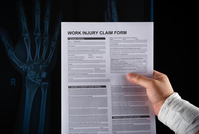 Studio shot of man reading work injury claim form with a wrapped hand on top of an X-ray film medical and insurance concept no royalty free stock photos
